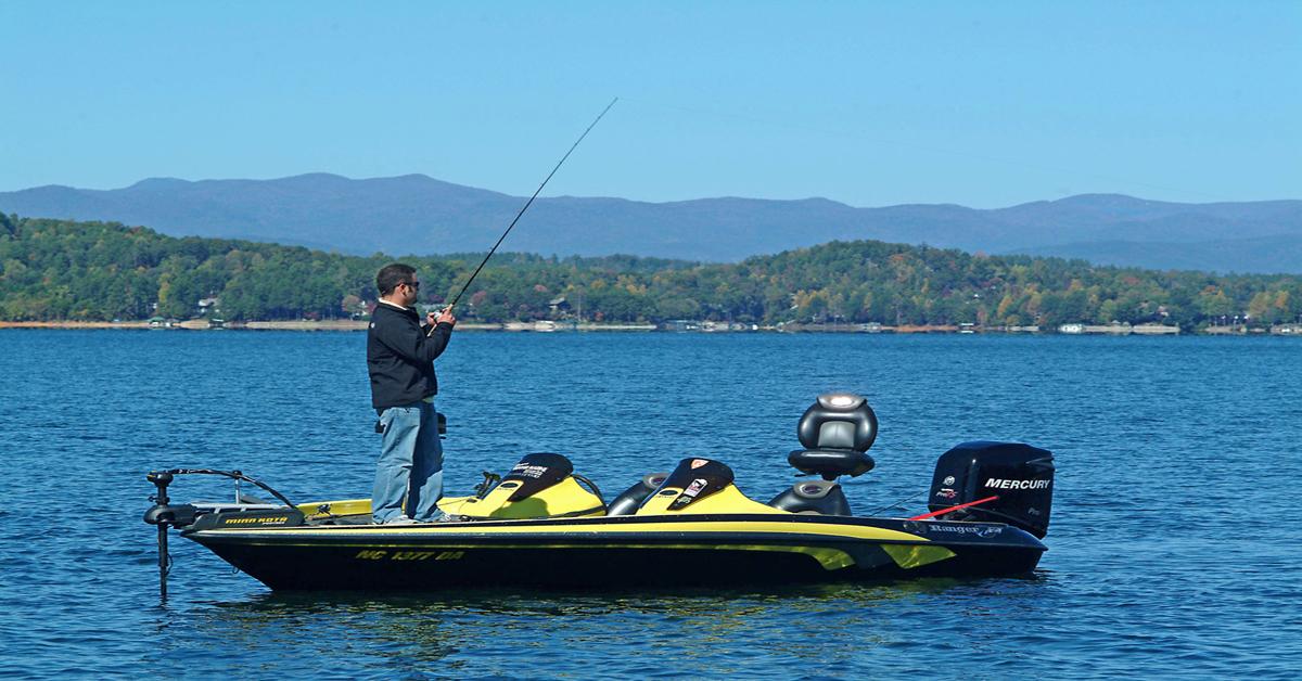 man fishing from boat on lake keowee